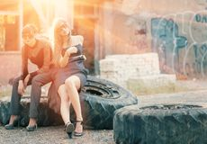 Two women sitting on a truck wheells backlit Royalty Free Stock Photo