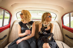 Two women sitting in vintage car and having coctails Royalty Free Stock Photos
