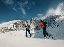 Two women ski walkers go up on the mountain top Stock Photo
