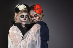 Two women in skull make-up Stock Images