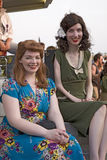 Two women smile as they are dressed in World War II 1940s vintage dresses Stock Photography