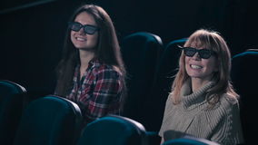 Two women are smiling in the cinema. Two women are watching the 3D movie in the cinema. Women are smiling stock video footage