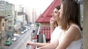 Two women smiling and laughing on balcony. Slow motion stock footage
