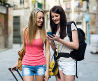 Two women smiling with luggage and using the map Royalty Free Stock Images