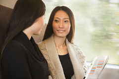 Two Women Smiling and  Talking on a Train Stock Photos