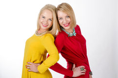 Two women smiling, in yellow and red dresses Stock Image