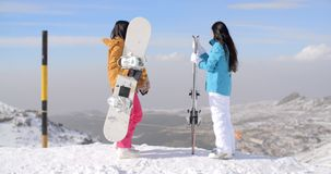 Two women snowboarders enjoying the winter view. From a snowy mountain summit at a ski resort standing with their backs to the camera stock video
