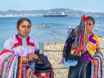 Two women with souvenirs. ACAPULCO, MEXICO - MARCH 11, 2006 : Two Mexican women on a shore with traditional clothing and souvenirs with Queen Mary 2 cruise ship Royalty Free Stock Image