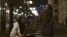 Two women are speaking on the night street in historic center of european city. Two women are speaking on the night pedestrian street in historic center of stock video