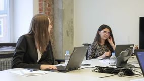 Two women speaking while sitting at table in company. Young professionals are located at big desk with black pc and discuss working matters, looking at screens stock footage