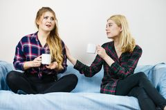 Female comforting her friend. Two women spending time together on sofa drinking tea. Female complaining, the other one comforting her. Perks of friendship Stock Photos