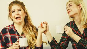 Female comforting her friend. Two women spending time together on sofa drinking tea. Female complaining, the other one comforting her. Perks of friendship Royalty Free Stock Images