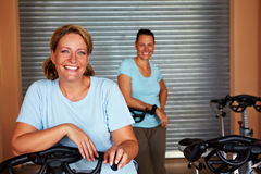 Two women in spinning room. Two smiling women standing in spinning room in a gym Stock Image