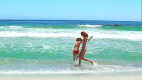 Two women splashing each other. In front of the ocean stock video footage