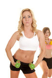 Two women sports bras one in front green weights Royalty Free Stock Photo
