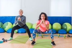Two women in sportswear doing bodyweight squats while training indoors at sports hall.  royalty free stock photos