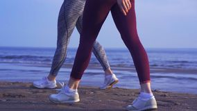 Two women in sportswear and sneakers are walking along the sandy shore at the very edge of the water of a large river. stock footage