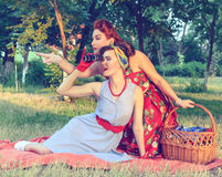 Two women spying. Two spy girl hiding face behind the book pin-up Stock Photo
