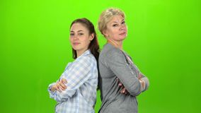 Two women stand back to back and cross their arms and show a thumbs-up. Green screen. Side view. Two women stand back to back and cross their arms smiling and stock footage
