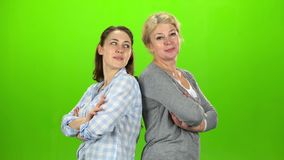 Two women stand back to back and cross their arms. Green screen. Side view. Two women stand back to back and cross their arms smiling and look straight. Green stock footage
