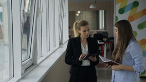 Two women stand in corridor near windows and discuss plans for today. Executive director, blonde woman who is dressed in black business costume, attentively stock video