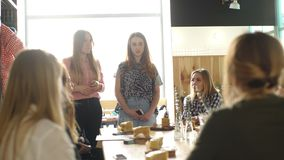 Two women stand in front of a group of women. Meeting girls in cafes stock video footage