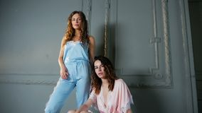 Two women stand in light clothing. In the studio stock video footage