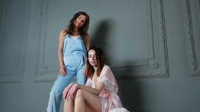 Two women stand in light clothing. In the studio stock video
