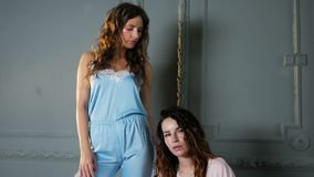 Two women stand in light clothing. In the studio stock footage