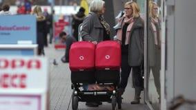 Two women stand near tweens strollers, talking. Two women stand near tweens red strollers, talking stock footage