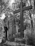 Two women stand next to a wooden cross Stock Image