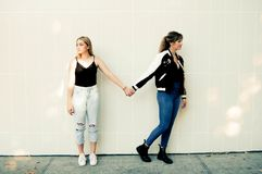 Two Women Standing Against Wall Stock Images