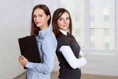 Two women standing back to back against the window Royalty Free Stock Image