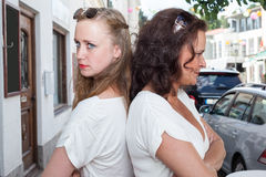 Two Women Standing Back to Back on City Street Royalty Free Stock Photo