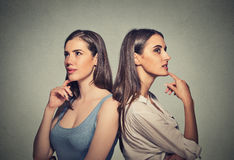 Two women standing back to back not speaking to each other Royalty Free Stock Photos