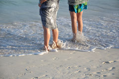 Two Women Standing on the Beach. As the Surf Rolls in Royalty Free Stock Photos