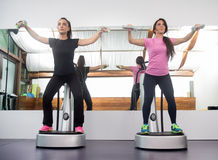 Two women standing exercise weights, fitness equipment similar t. O Power Plate Royalty Free Stock Photo