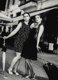 Two women standing inn front of bistro. Two female standing in the street outside cafe royalty free stock photos