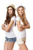 Two women standing leaning on each other. Leaning on each other. Two happy girls in straw hats and white tshirts standing back to back, against white background Royalty Free Stock Images