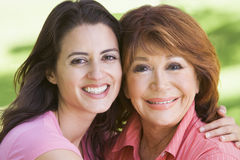 Two women standing outdoors smiling Stock Photos