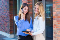 Two women standing outside looking at tablet. Two young women standing outside near bricked building entrance and looking at tablet. Brunette in blue shirt Stock Photography