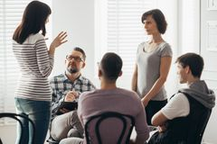 Two women standing and talking during group therapy with psychologist stock photo