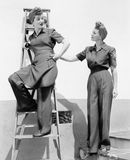 Two women standing together on a ladder and stairs Stock Photo