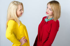 Two women standing, in yellow and red dresses Stock Images