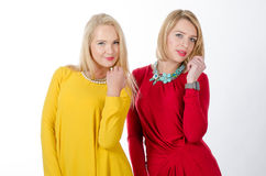Two women standing, in yellow and red dresses Royalty Free Stock Photos