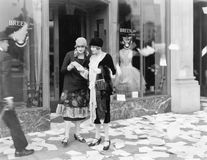 Two women in the street reading papers being thrown down from an office Stock Photo