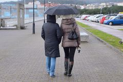 Two women on the street with umbrellas in the rain. Image of two women on the street with umbrellas in the rain Royalty Free Stock Image