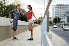 Two women stretching feet Royalty Free Stock Photos