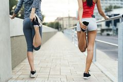 Two women stretching feet. Before jogging Royalty Free Stock Photo