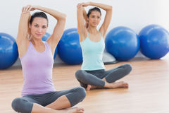 Two women stretching hands in fitness studio Royalty Free Stock Photography